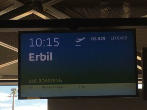 [Image description: photograph of the information board at the airport, showing 10:15 flight to Erbil.]