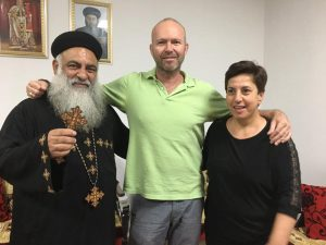 [Image description: Father Chris with Father Schnuder (left) and Onur (right). They are in a room with some framed icons behind them. Father Schnuder is holding up an ornate wooden cross. They are looking at the camera and smiling.]