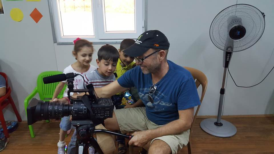 [Image description: Father Chris sitting in a room behind his video camera. Three children are next to him, intently fixated on the video camera and Father Chris's explanations.]