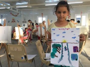 [Image description: a young girl holds up a painting she made. There are blue clouds in the sky, the sun is setting on the horizon. The focus of the painting is a long road disappearing into the horizon, in the middle of the paper, where a person is walking into the horizon carrying a bag and a walking stick. There are trees lining one side of the road and two houses on the other side of the road.]