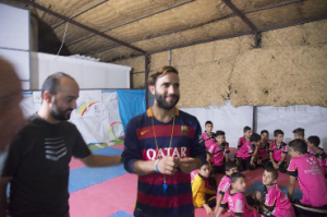 [Image description: Ninos Haddad, in a black shirt, and Allin, in a red-and-navy striped rugby shirt, stand in front of the camera but looking off to the side. Behind them, a group of boys sit on mats on a gym floor. The boys are wearing bright pink shirts.]
