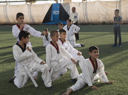 [Image description: a group of boys dressed in white martial arts gis pose for a camera off to the right. The boy in the front is doing the center splits, the other boys are doing fight stances with their arms.]
