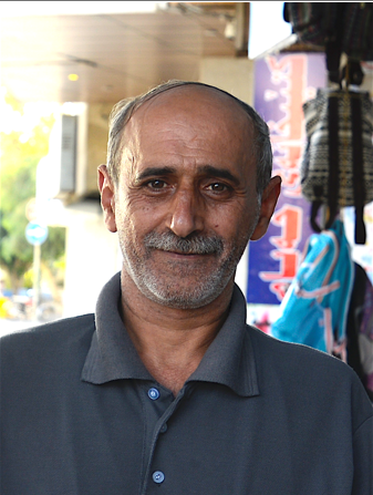[Image description: photo of Ashur, and Iraqi man. He is smiling at the camera. He has gray hair and a mustache, and is wearing a blueish-gray polo shirt.]
