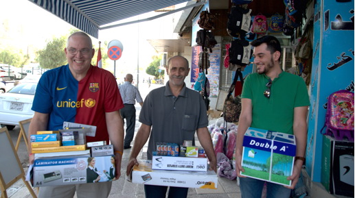 [Image description: Ashur and two other men are walking on the sidewalk outside the store, carrying boxes of paper, pens, a laminator machine, and other office supplies. They are all smiling.]
