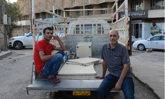 [Image description: Yusuf and Ashur sit on the bed of the truck, looking at the camera. There are a few boxes of supplies and more pieces of the desk in the bed of the truck.]