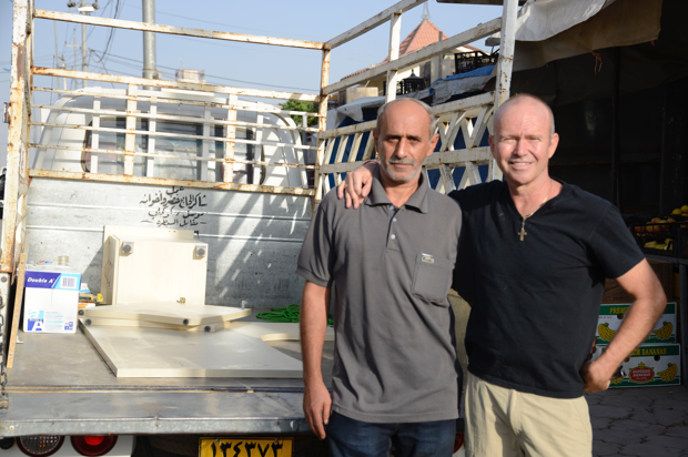 [Image description: Ashur and Father Chris stand next to the bed of the truck, looking at the camera and posing for the photo. They have their arm around the other's shoulders.]