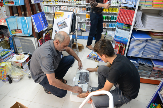 [Image description: Ashur and a young man kneel on the floor of a store, looking at a printer still in its plastic wrapping. There are shelves of books and notebooks around them.]