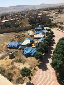 [Image description: photograph of several tents pitched in an empty lot.
