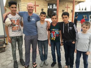 [Image description: Father Chris stands with five Iraqi boys in front of a building with crosses on the front. They are smiling, facing the camera, and have their arms around each other's shoulders.]