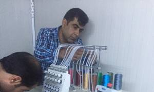 [Image description: A man arranges the threads on a sewing/embroidery machine. Another man is leaning over the maching, mostly off-camera, presumably setting up another part of the machine.]