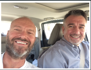 [Image description: selfie Fr. Chris, who has a beard, and Fr, Douglas Bazi. They are riding in a car, Fr. Bazi is in the driver's seat.]