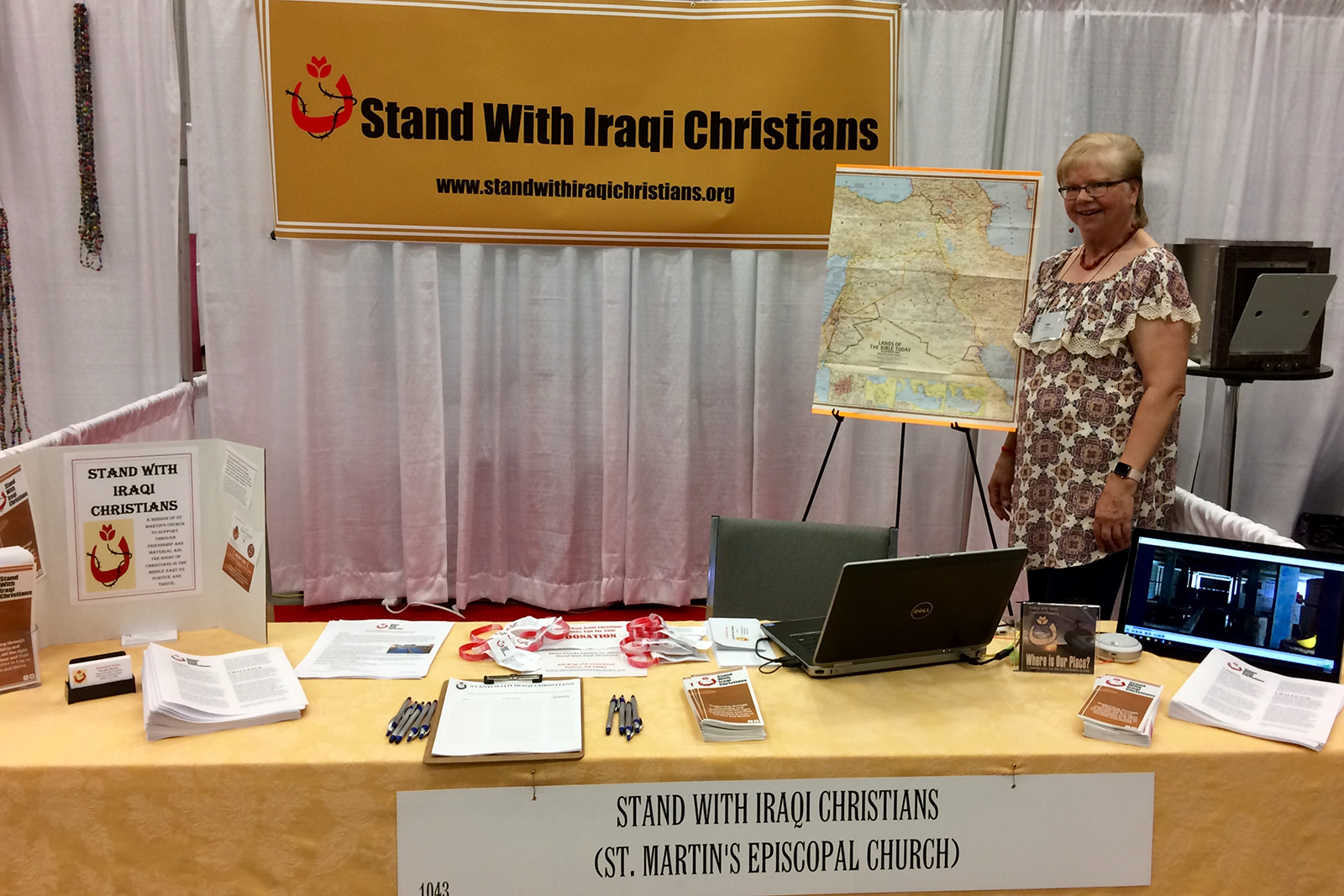 [Image description: SWIC Executive Director Deb Parker stands behind the SWIC booth table at the 2018 Episcopal Church General Convention. Behind her is a banner with the SWIC name and logo and an easel with a map of Iraq. The table has brochures, fliers, pens, etc.]