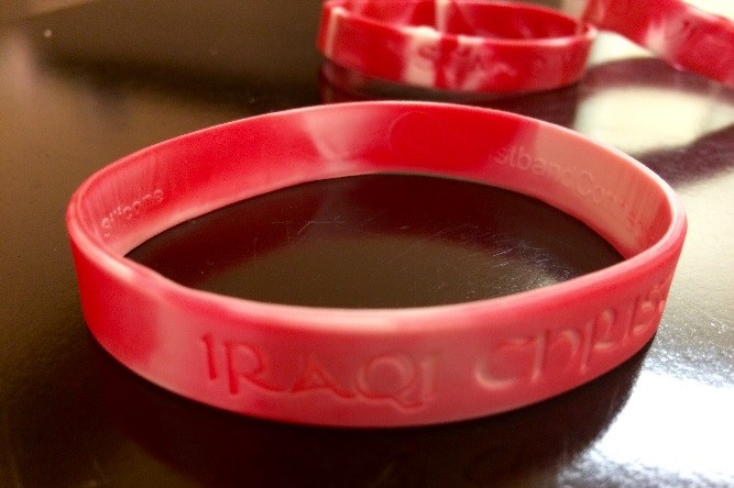 "[Image description: photograph of a red marbled plastic wristband on a table. The words ""IRAQI CHRISTIANS"" can be seen on the outside of the wristband.]"