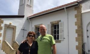 [Image description: photograph of Fr. Chris with Georgia standing in frontof a white church. They are smiling at the camera.]