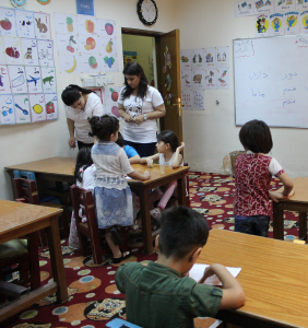[Image description: the inside of a classroom. Two adult women stand at a table, working with a student and looking over other student work. Other students, their backs to the camera, sit at nearby tables doing their work. There are educational posters on one wall and a whiteboard on the other wall.]