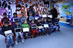 [Image description: elementary-aged students sit in two rows, facing he camera, displaying the electronic tablets donated to their school by SWIC, thanks to your generous donations.]